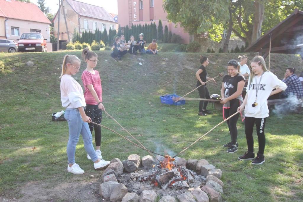 Dziewczynki ze Szkoły Podstawowej w Cedyni smażą kiełbaski nad ogniskiem.