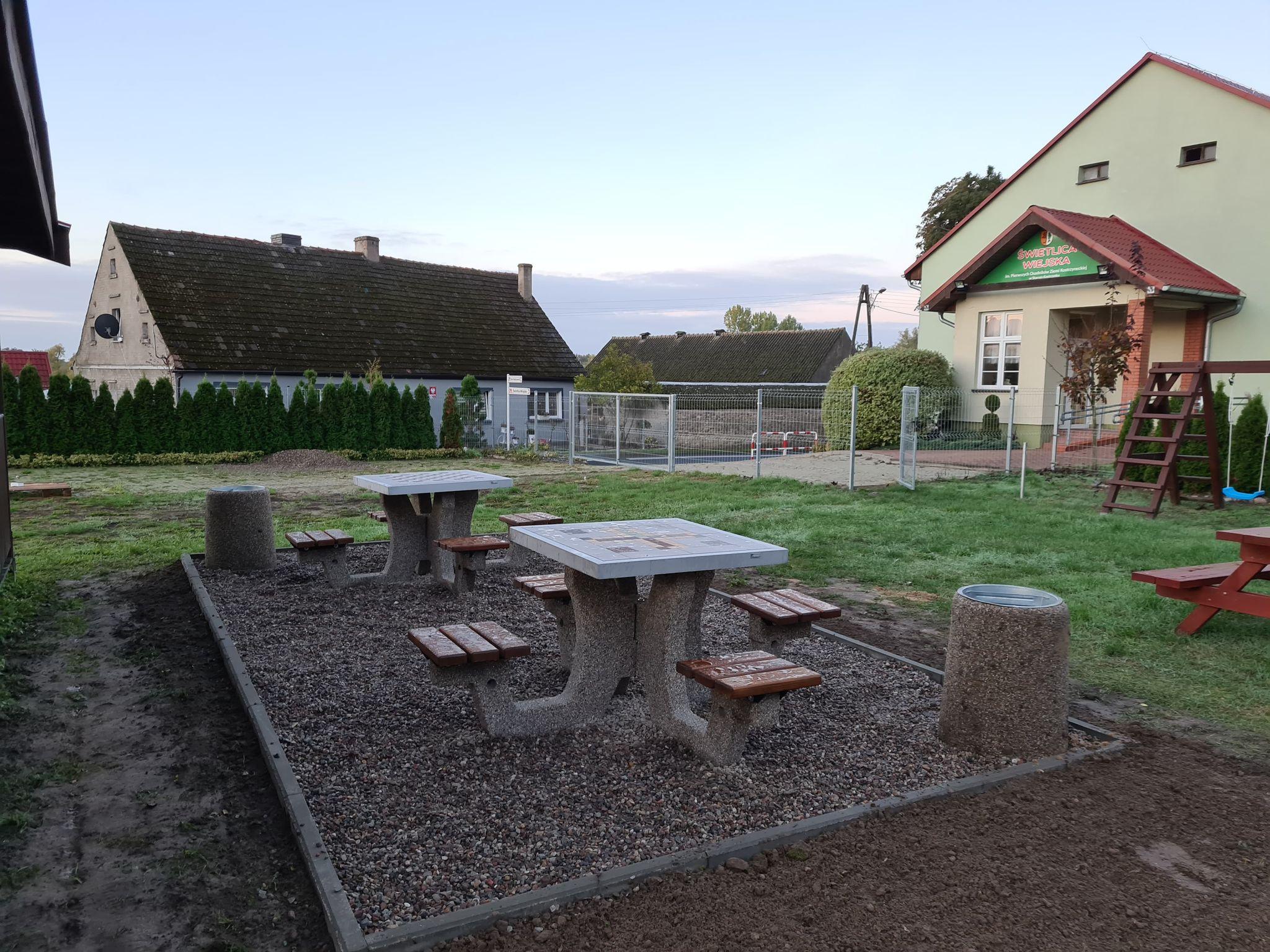 Dwa betonowe stoły z grami planszowymi oraz kosze na śmieci zamontowane na placu zabaw w Starym Kostrzynku.